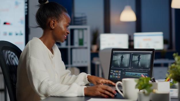 Schwarzer begeisterter videofilmer, der film auf professionellem laptop bearbeitet editing