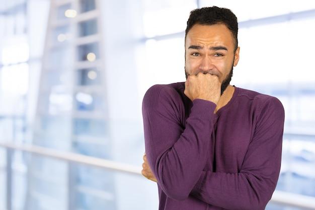 Schwarzer besorgter betonter junger mann, der kamera betrachtet