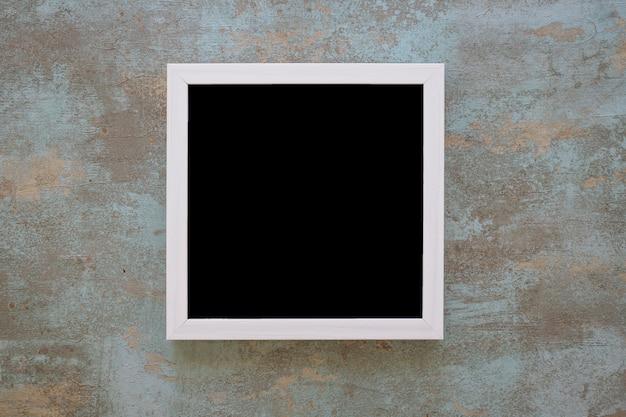 Schwarzer bilderrahmen auf schmutzwand