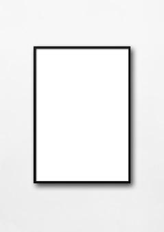 Schwarzer bilderrahmen, der an einer weißen wand hängt.
