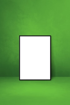 Schwarzer bilderrahmen, der sich an eine grüne wand lehnt. leere mockup-vorlage