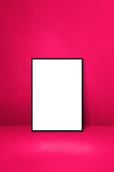 Schwarzer bilderrahmen, der sich an eine rosa wand lehnt. leere mockup-vorlage