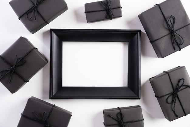 Schwarzer bilderrahmen mit geschenkbox auf weißem hintergrund. schwarzer freitag