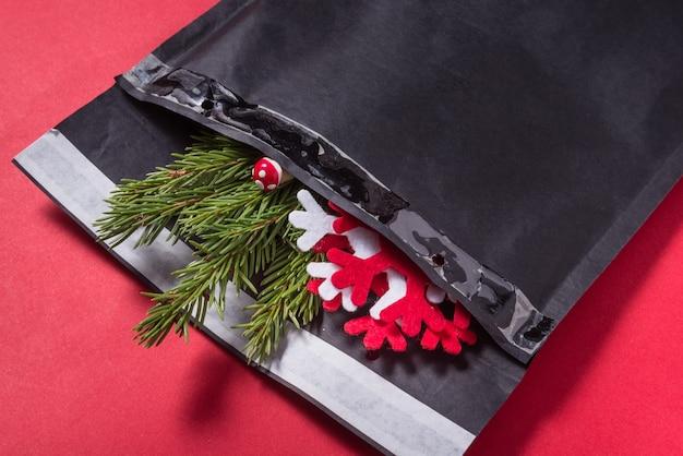 Schwarzer blasenumschlag verziert mit weihnachtsbaumverzierung auf rot