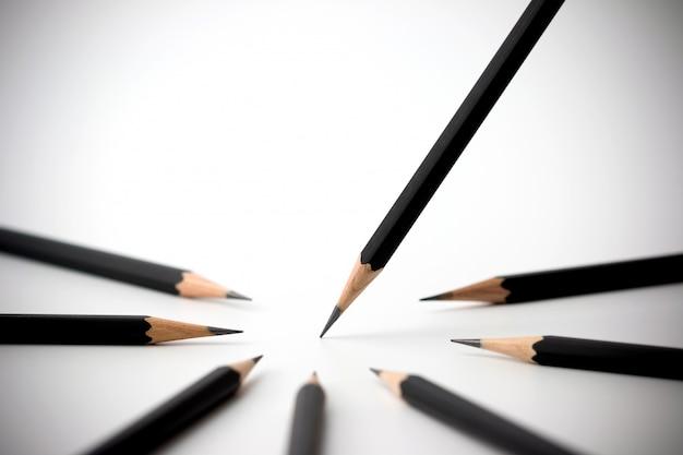 Schwarzer bleistift, der von der menge von viel identischen schwarzen gefährten auf weißer tabelle herausragt.