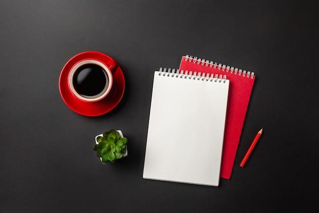 Schwarzer bürodesktop mit rotem tasse kaffee und notizbuch. draufsicht mit kopienraum.