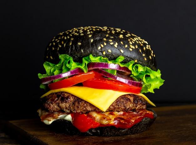 Schwarzer burger auf einem schwarzen. cheeseburger. rezepte. fast food.