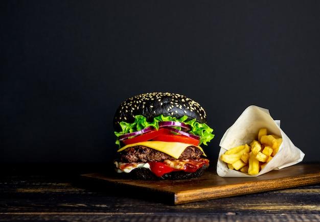 Schwarzer burger auf einem schwarzen hintergrund. cheeseburger. rezepte. fast food. amerikanische küche.