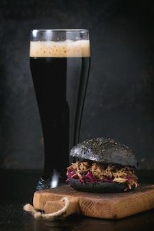 Schwarzer burger mit dunklem bier