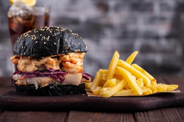 Schwarzer burger mit fisch und garnelen, fishburger mit garnelen und pommes frites