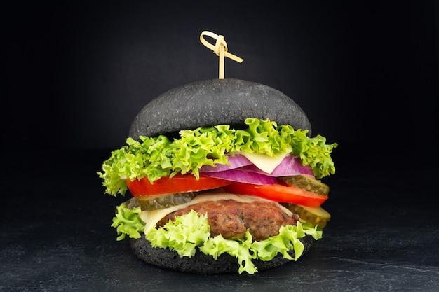 Schwarzer burger mit käse. cheeseburger mit schwarzem brötchen