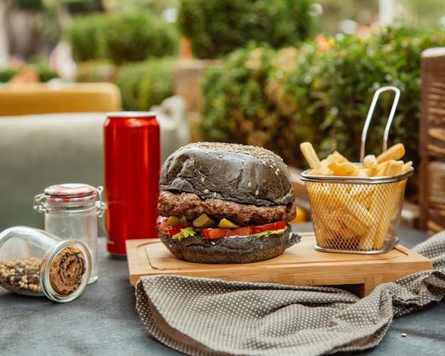 Schwarzer burger mit pommes und cola