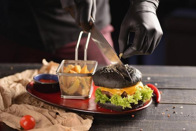 Schwarzer burger mit pommes und soße. in einer roten platte auf einem holztisch