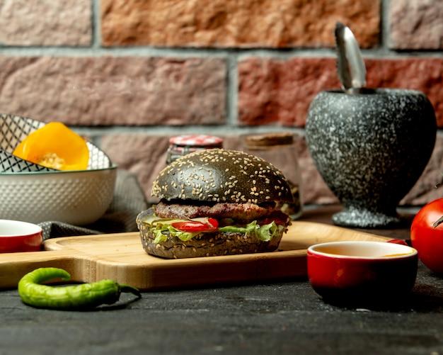 Schwarzer burger mit rindfleisch-tomaten-paprika-salat und eingelegter gurke