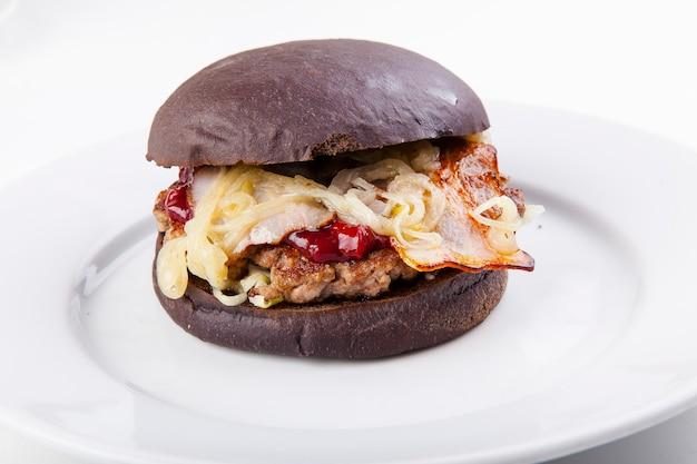Schwarzer burger mit speckschnitzel röstzwiebeln und kirschsauce