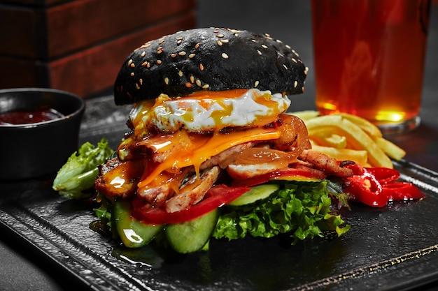 Schwarzer cheeseburger mit gemüse hähnchenfilet karamellisierten zwiebeln und spiegelei
