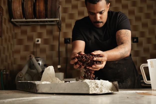 Schwarzer chef kocht kuchen. baker fügt einige trockene früchte in mehl in einen metalltopf, um es zu mischen und in seiner professionellen konditorei einen kuchenteig herzustellen