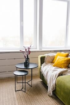 Schwarzer couchtisch mit vasen und zweigen mit blättern auf dem teppich in einem echten foto eines hellen wohnzimmers mit einer decke und gelben kissen auf einem grünen sofa in einem hellen wohnzimmer
