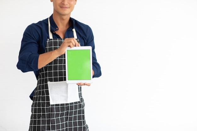 Schwarzer digitaler tablet-pc mit leerem grünem bildschirm. porträt des lächelnden jungen hispanischen mannes in der schürze, der die kamera lokalisiert auf weißem hintergrund betrachtet
