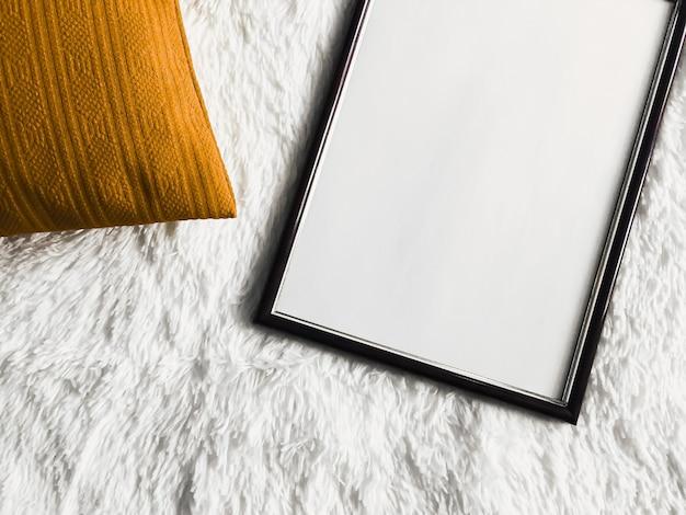 Schwarzer dünner holzrahmen mit leerem exemplar als poster-fotodruck-modell goldenes kissenkissen und flauschige weiße decke flach hintergrund und kunstprodukt-draufsicht
