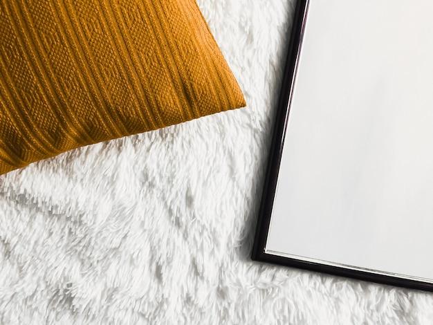 Schwarzer, dünner holzrahmen mit leerem exemplar als poster-fotodruck-modell, goldenes kissenkissen und flauschige weiße decke, flacher hintergrund und kunstprodukt-draufsicht