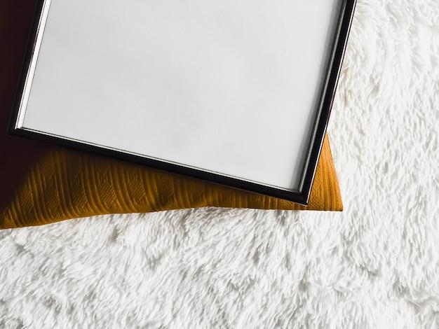 Schwarzer dünner holzrahmen mit leerem exemplar als poster-fotodruck-modell goldenes kissenkissen und ...