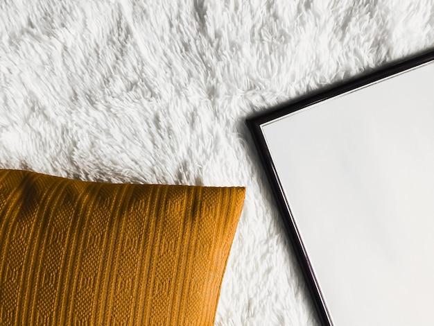 Schwarzer dünner holzrahmen mit leerem exemplar als posterfotodruckmodell goldenes kissenkissen und ...