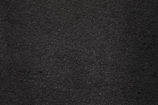 Schwarzer dunkler asphalt mit feinkörniger textur. nahaufnahmefoto