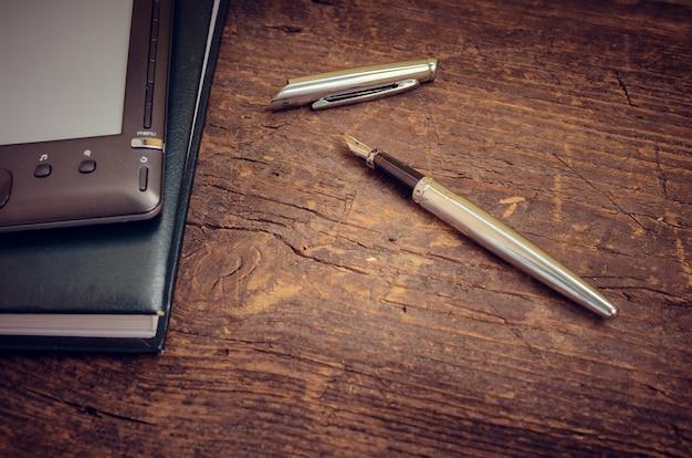 Schwarzer ereader mit notizbuch- und tintenstift