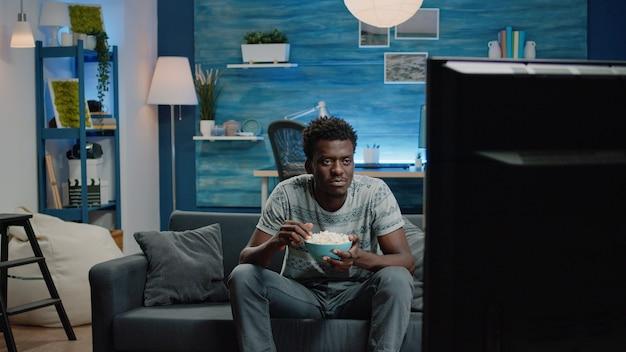 Schwarzer erwachsener, der sich im fernsehen eine komödie ansieht