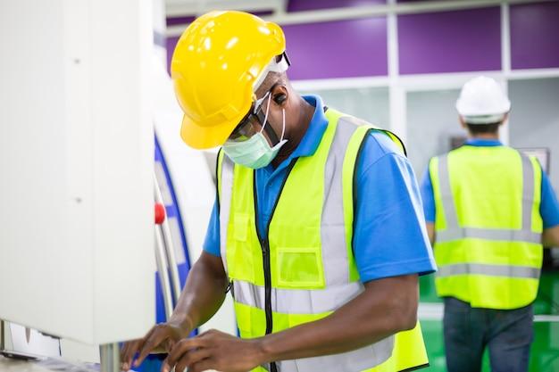 Schwarzer fabrikmann arbeiter, der medizinische gesichtsmaske trägt, die an industriemaschine arbeitet