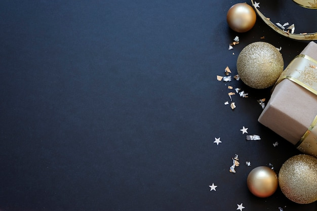 Schwarzer festlicher hintergrund mit goldener dekoration. weihnachtsgrußkarte mit platz für text
