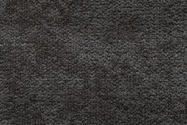 Schwarzer flauschiger hintergrund aus weichem, flauschigem stoff, textur aus leichtem windelgewebe,