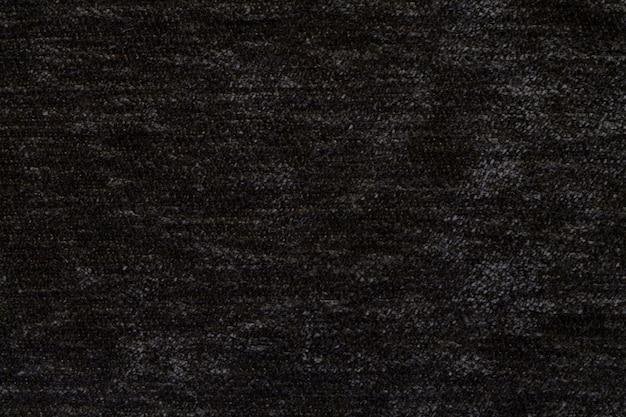 Schwarzer flauschiger hintergrund des weichen, flauschigen stoffes. textur der textilen nahaufnahme.