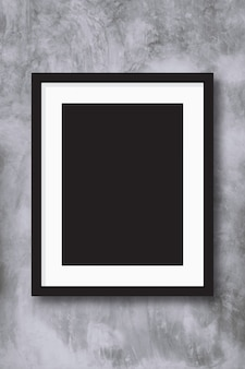 Schwarzer fotorahmen auf concreate wandhintergrund.