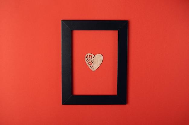 Schwarzer fotorahmen mit dem hölzernen herzen innen. valentinstag konzept. flache lage, draufsicht.