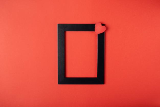Schwarzer fotorahmen mit dem roten holzherz. valentinstag konzept. flache lage, draufsicht.