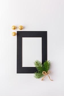 Schwarzer fotorahmen mit goldenen weihnachtskugeln und fichtenzweig auf weiß