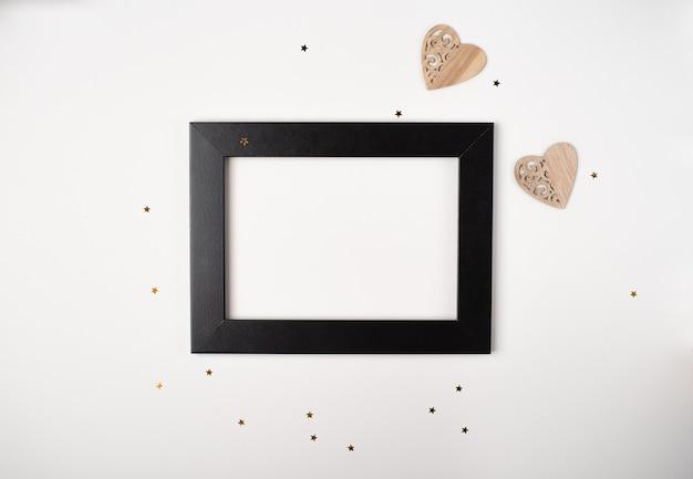 Schwarzer fotorahmen mit holzherzen und kleinen goldenen sternen auf weiß. valentinstag konzept.