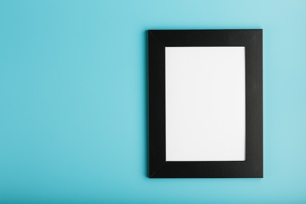 Schwarzer fotorahmen mit leerem raum auf blauem hintergrund.