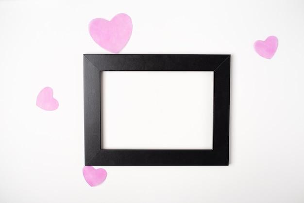 Schwarzer fotorahmen mit rosa herzen auf dem hellen (weißen) hintergrund. valentinstag konzept. flache lage, draufsicht.