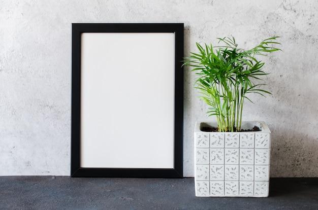 Schwarzer fotorahmen und schöne pflanze im betontopf. zimmer im skandinavischen stil.