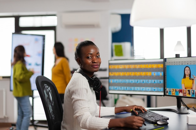 Schwarzer fotoretuscher, der in die kamera lächelt, die in einer kreativen medienagentur sitzt und das kundenbild auf dem pc mit zwei displays retuschiert