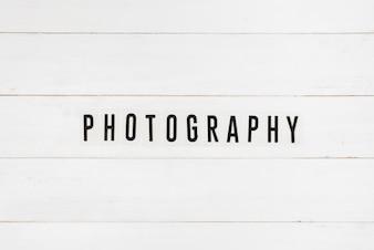 Schwarzer Fototext auf weißem Holztisch