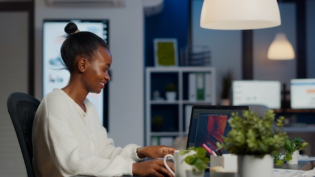 Schwarzer freiberuflicher spieleentwickler, der auf der tastatur tippt und ein neues level von videospielen entwickelt. afrikanischer pro-spieler testet das spiel über der level-schnittstelle um mitternacht vom geschäftsbüro mit laptop.