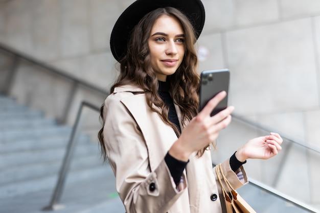 Schwarzer freitag, frau, die smartphone und einkaufstasche beim stehen auf dem einkaufszentrum hält