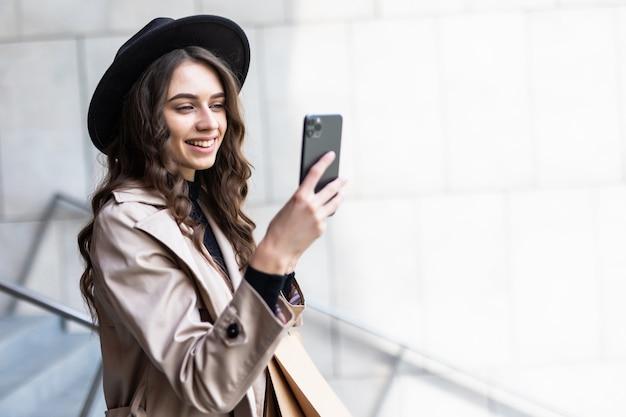 Schwarzer freitag, frau, die smartphone und einkaufstasche beim stehen auf der wand des einkaufszentrums hält