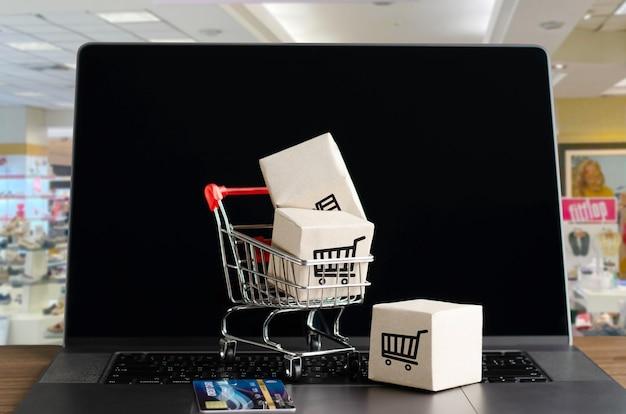 Schwarzer freitag im e-commerce-konzept, online-shopping und kundenerlebnis : box mit warenkorb auf der tastatur, warenkorbsymbol auf dem computer attribution-noncommercial-sharealike