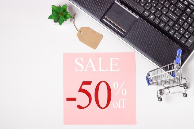 Schwarzer freitag. laptop, notizbuch und einkaufswagen auf weißem hintergrund