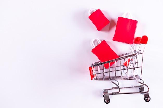 Schwarzer freitag . laufkatzenwagen und rote papiereinkaufstaschen auf weiß. copyspace.